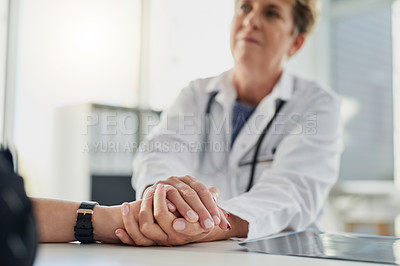 Buy stock photo Cropped shot of a mature female doctor holding a patient's hand in comfort in her office in the hospital
