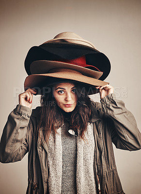 Buy stock photo Studio shot of a young woman wearing a pile of hats against a brown background