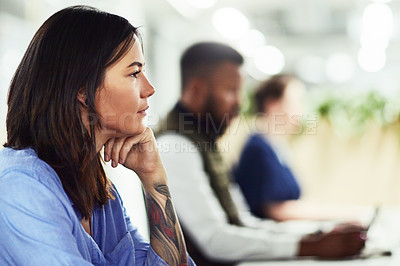 Buy stock photo Shot of a young designer working in an office with her colleagues in the background