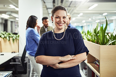 Buy stock photo Portrait of a young designer standing in an office with her colleagues in the background