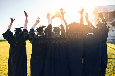 Buy stock photo Rearview shot of a group of students standing in a line with their arms raised on graduation day