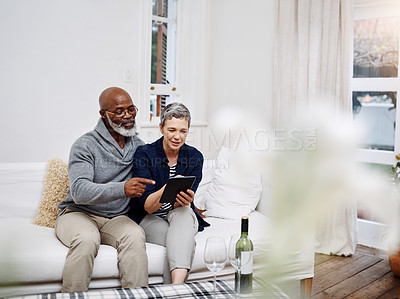 Buy stock photo Shot of an affectionate senior couple using a tablet while relaxing on the sofa at home