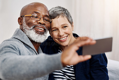 Buy stock photo Shot of an affectionate senior couple taking selfies while relaxing on the sofa at home
