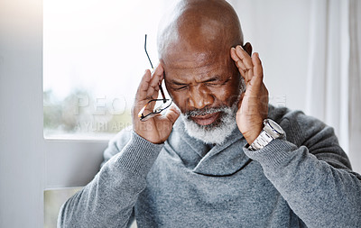 Buy stock photo Shot of a handsome senior man suffering with a headache at home