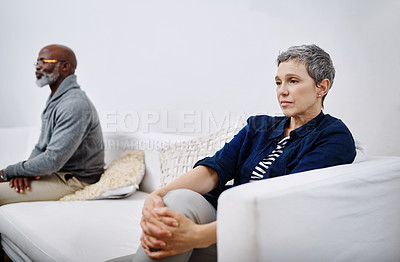 Buy stock photo Shot of an unhappy senior couple sitting separately on a couch after having an argument at home