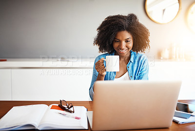 Buy stock photo Shot of an attractive young woman having a cup of coffee while working on her laptop at home