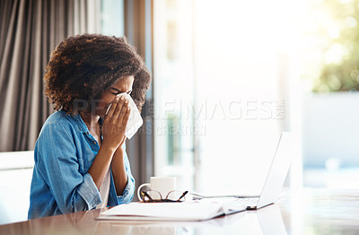 Buy stock photo Portrait of a young woman blowing her nose with a tissue while working at home