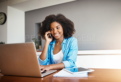 Buy stock photo Shot of an attractive young woman taking a phone call while working on her laptop at home