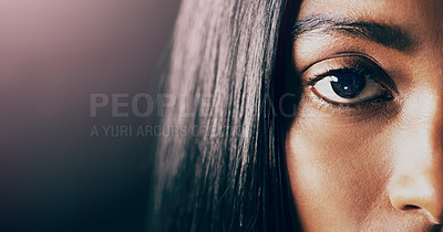 Buy stock photo Closeup studio portrait of a beautiful young woman's eye against a dark background