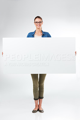 Buy stock photo Studio portrait of a young woman holding a blank placard against a grey background