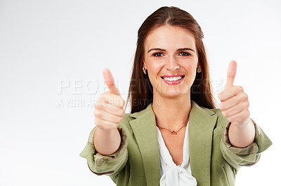 Buy stock photo Studio portrait of a young woman showing a thumbs up gesture against a grey background