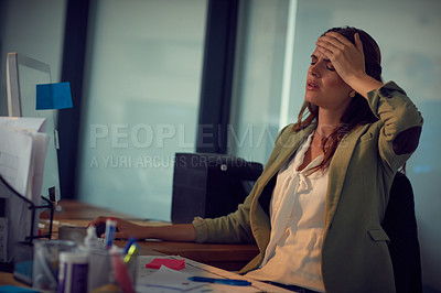 Buy stock photo Shot of a young businesswoman looking stressed while working late at the office