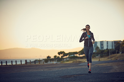 Buy stock photo Shot of a sporty young woman exercising outdoors