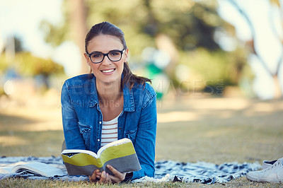 Buy stock photo Portrait of an attractive young woman reading a book while relaxing in the park