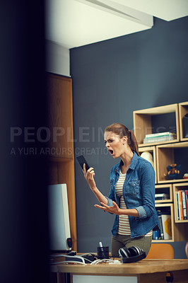 Buy stock photo Shot of a young businesswoman using a mobile phone and looking angry in a modern office
