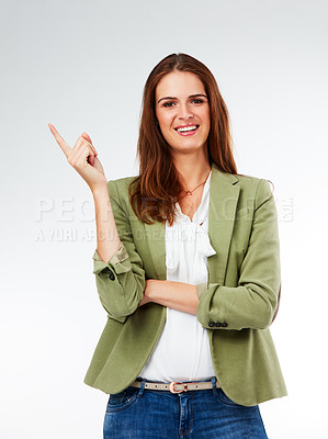 Buy stock photo Studio portrait of a young woman pointing against a grey background