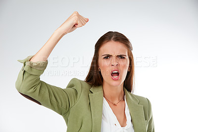 Buy stock photo Studio portrait of a young woman shaking her fist in anger against a grey background