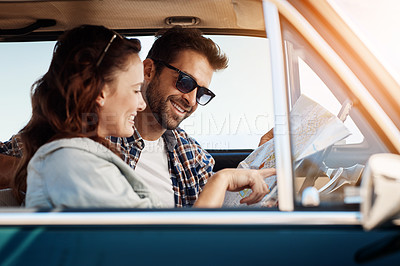 Buy stock photo Cropped shot of an affectionate couple checking a map while enjoying a road trip