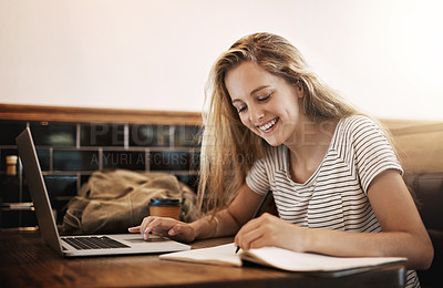 Buy stock photo Cropped shot of a focussed young student using her laptop to study at a table in a cafe