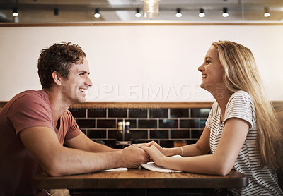 Buy stock photo Cropped shot of a happy young student couple holding hands while studying together at a cafe