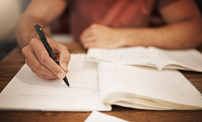 Buy stock photo Cropped shot of an unrecognizable young male student studying alone at a table in a cafe