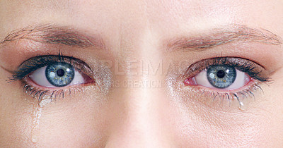 Buy stock photo Closeup shot of a young woman's tearful eyes in studio