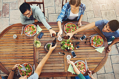 Buy stock photo High angle shot of a group young friends holding drinks and toasting together outside around a table