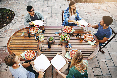 Buy stock photo High angle shot of a group of friends sitting around a table and enjoying pizza together outdoors