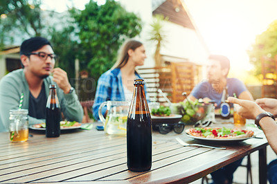 Buy stock photo Shot of a beer bottle on a table with a group of people enjoying themselves in the background