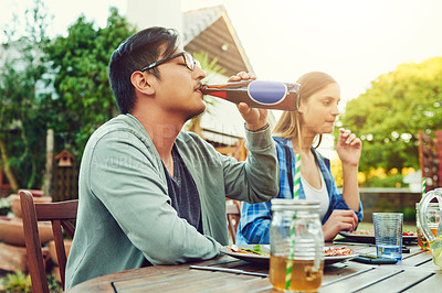 Buy stock photo Shot of a young man having a sip of a beer while sitting around a table in an outdoor gathering amongst friends