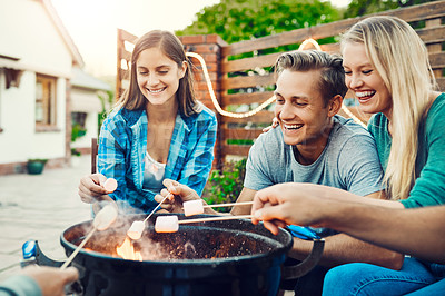Buy stock photo Shot of a group cheerful young friends holding up marshmallows on sticks over a fire outside