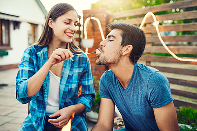 Buy stock photo Shot of a young cheerful man being fed a marshmallow by his girlfriend while relaxing outside