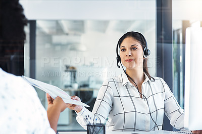 Buy stock photo Shot of a call centre agent passing paperwork to her colleague in an office