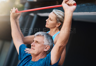 Buy stock photo Shot of a mature man stretching his arm muscles with an elastic band while being assisted by his wife