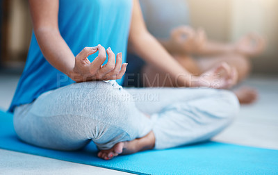 Buy stock photo Shot of an unrecognizable woman meditating on her yoga mat with her husband in the background