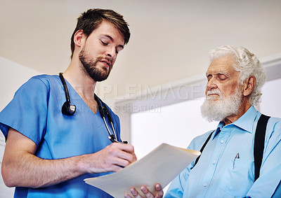 Buy stock photo Shot of a young doctor going through medical records with a senior patient at a hospital