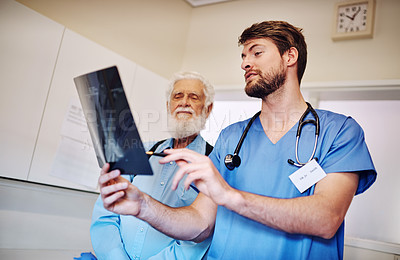 Buy stock photo Shot of a young doctor and his senior patient looking at an x-ray together