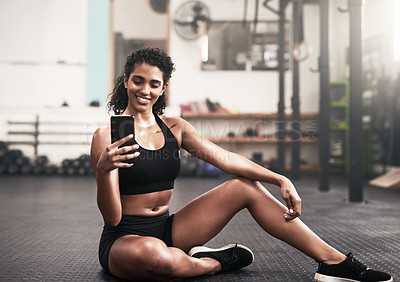Buy stock photo Shot of a sporty young woman taking photos on her cellphone in a gym
