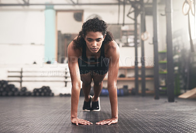 Buy stock photo Shot of a sporty young woman doing pushups in a gym