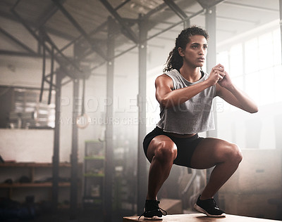 Buy stock photo Shot of a sporty young woman box jumping in a gym