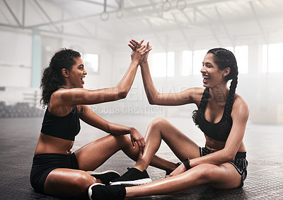Buy stock photo Shot of two sporty young women giving each other a high five while working out at the gym