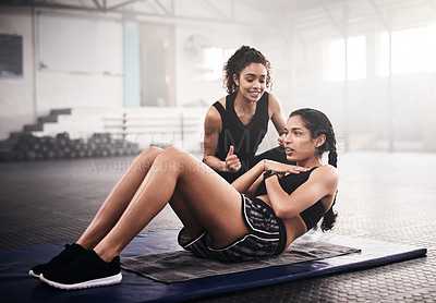Buy stock photo Shot of a sporty young woman working out with a fitness instructor at the gym