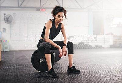 Buy stock photo Portrait of a sporty young woman sitting on a barbell in a gym