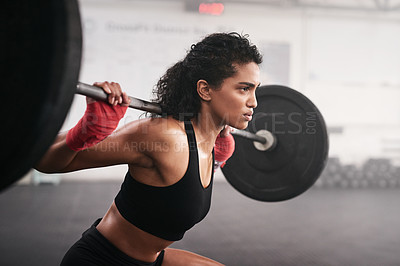 Buy stock photo Shot of a sporty young woman lifting a barbell in a gym