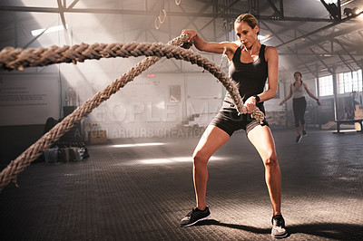 Buy stock photo Shot of a sporty young woman working out with battle ropes in a gym