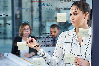 Buy stock photo Shot of a young businesswoman presenting notes on a glass wall to her colleagues in an office