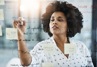 Buy stock photo Shot of a young businesswoman brainstorming on a glass wall in an office