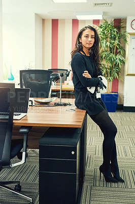 Buy stock photo Full length portrait of an attractive young businesswoman leaning against her desk in the office