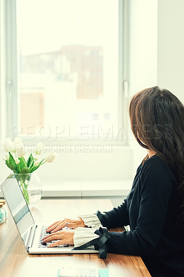 Buy stock photo Rearview shot of an unrecognizable young businesswoman working on her laptop in the office
