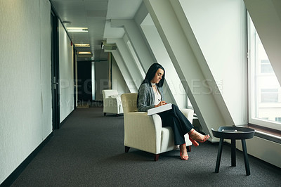 Buy stock photo Full length shot of an attractive young businesswoman writing notes while sitting in her office